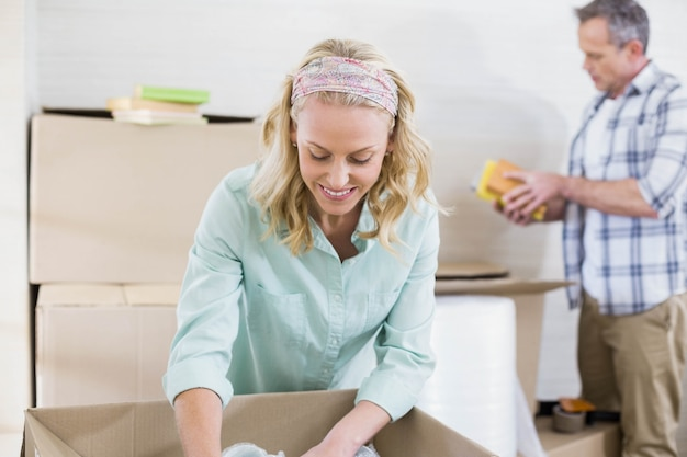 Smiling woman packing mug in a box with her husband behind her Premium Photo