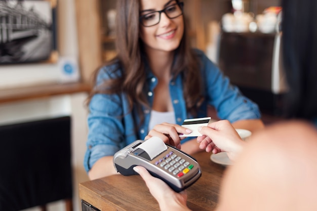 Smiling woman paying for coffee by credit card Free Photo