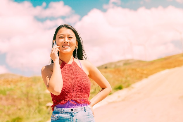 Smiling woman phoning in countryside Free Photo