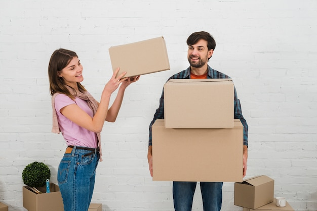 Smiling woman placing the stack of cardboard boxes over his husband's hand Free Photo