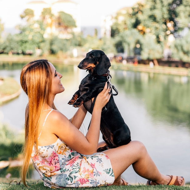 Smiling woman playing with her dog near the lake Free Photo