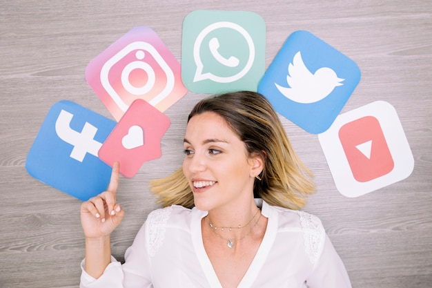 Smiling woman pointing upward in front of wall with social networking icons Premium Photo