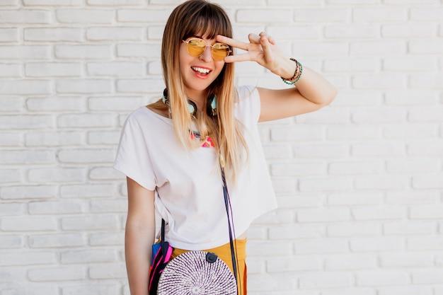 イヤホンで白いレンガの壁を越えてポーズと兆しを見せて笑顔の女性。 無料写真