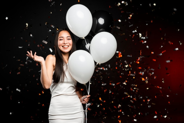 Smiling woman posing with balloons at new years party Free Photo