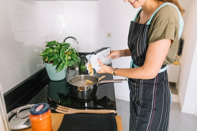 Smiling woman pouring rigatoni pasta in the sauce pan over the electric stove Free Photo