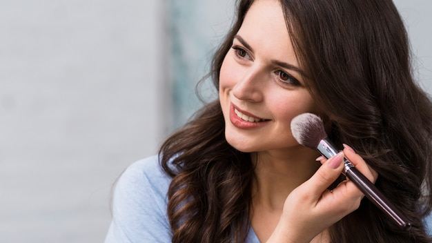 笑顔の女性が頬を粉に 無料写真