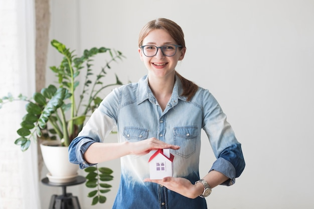Smiling woman protecting house model at office looking at camera Free Photo