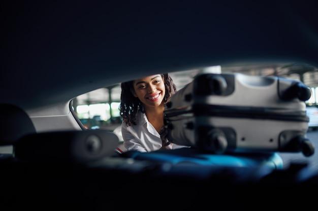 웃는 여자는 주차에 차에 가방을 넣습니다. 여성 여행자는 수하물, 차량 주차장, 많은 가방을 가진 승객을 포장합니다. 자동차 근처 수하물 소녀 프리미엄 사진