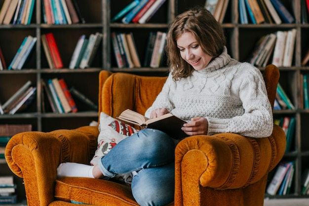 Smiling woman reading in armchair Free Photo