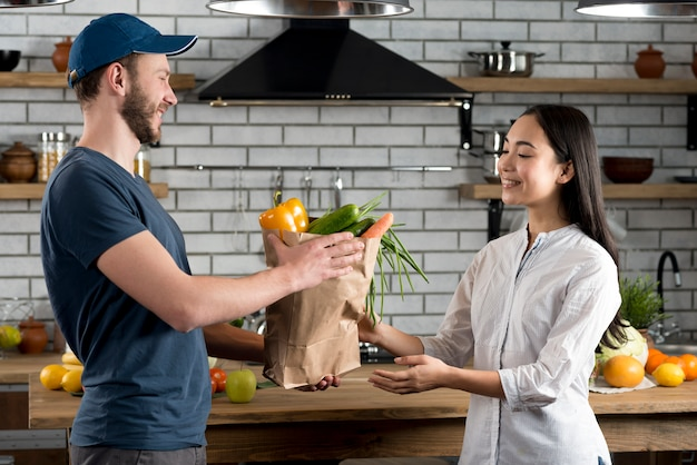 Smiling woman receiving grocery from delivery man in kitchen Free Photo