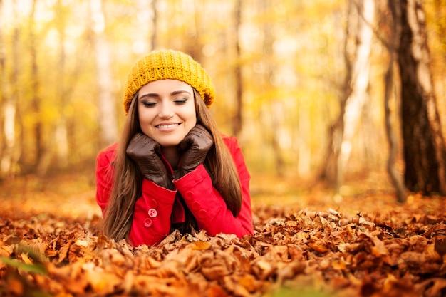 Улыбающаяся женщина отдыхает в парке осенью Бесплатные Фотографии