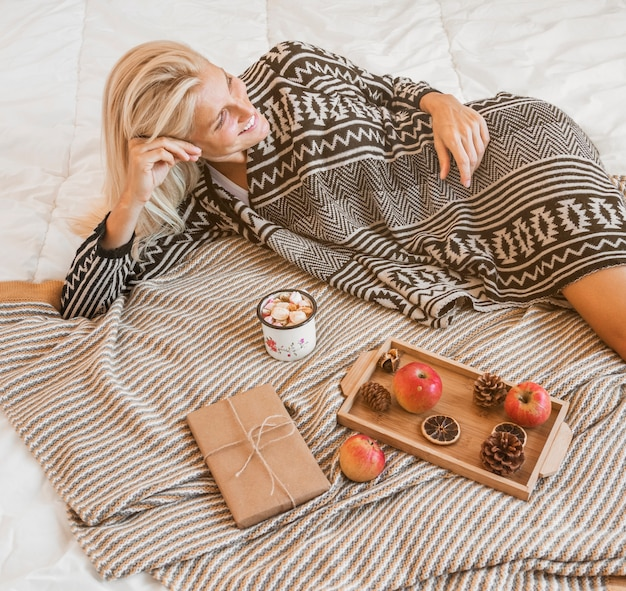 Smiling woman relaxing near hot beverage and gift Free Photo