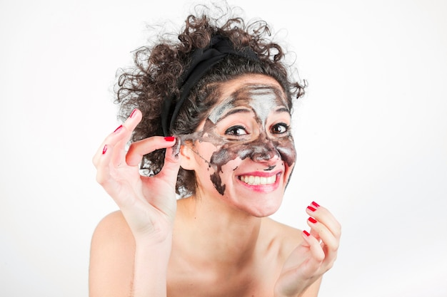 Smiling woman removing purifying mask from her face over white background Premium Photo