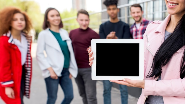 Smiling woman showing blank digital tablet in front of defocused people Free Photo