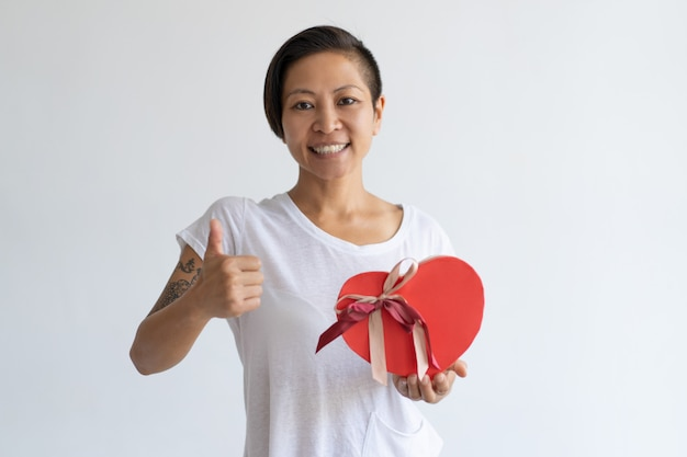 Smiling woman showing heart shaped gift box and thumb up Free Photo