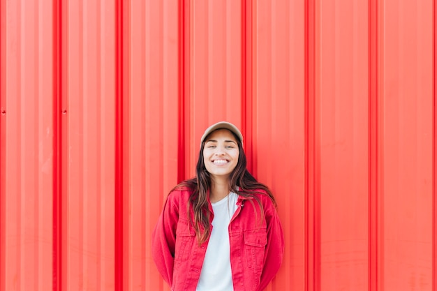 Smiling woman standing against red corrugated background Free Photo