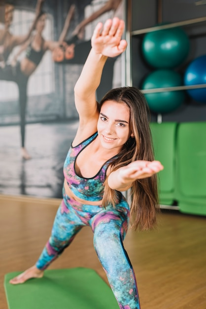 Smiling woman stretching her arms and looking at camera in gym Free Photo