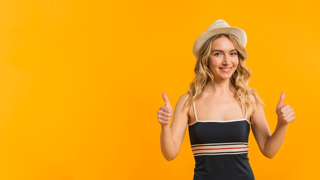 Smiling woman in summer clothes showing thumbs up Free Photo