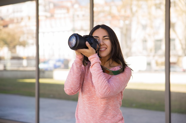 Smiling woman taking photos with camera outdoors Free Photo
