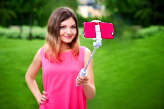 Smiling woman taking selfie on cellphone with stick outdoors Premium Photo