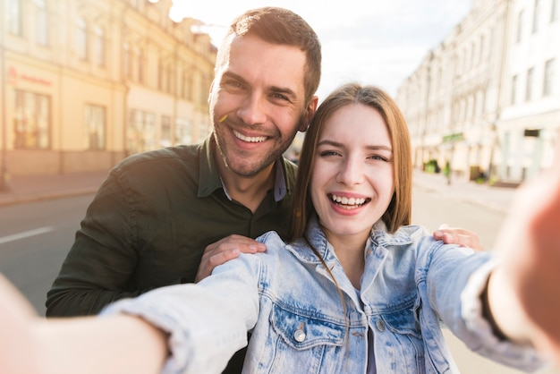 Smiling woman taking selfie with her boyfriend on road Free Photo