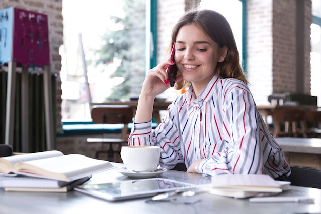 Smiling woman talking on smartphone Free Photo