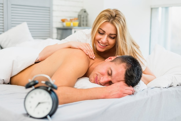 Smiling woman waking up man near snooze in bed Free Photo