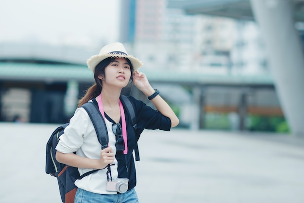 Smiling woman walking outdoors, young lady admiring city sight with walkway and buildings in background. Free Photo