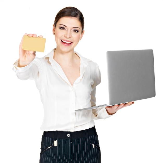 Donna sorridente in una camicia bianca con laptop e carta di credito isolato su bianco. Foto Gratuite