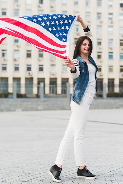 Smiling woman with american flag in city Free Photo