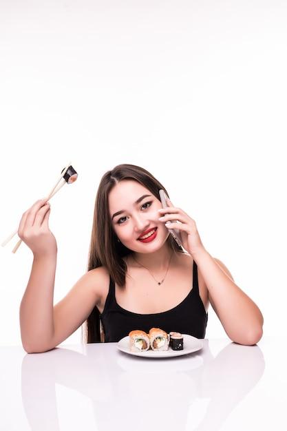 黒い髪と赤い唇で笑顔の女性が彼女の電話で話している彼女の手で木の箸を持ってsuushiロールを味わう 無料写真