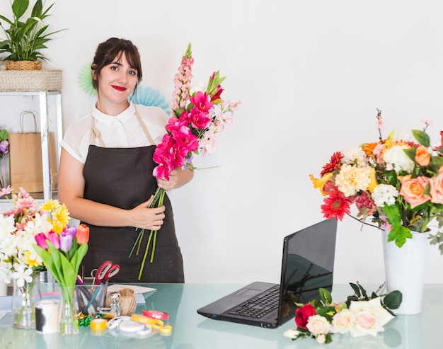 Smiling woman with bunch of flowers standing in floral shop Free Photo