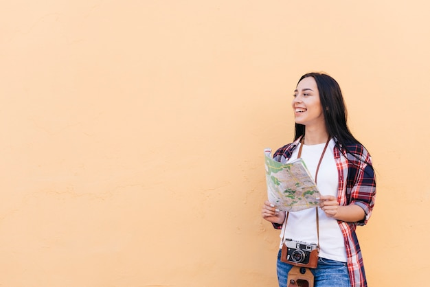 Smiling woman with camera around her neck holding map Free Photo