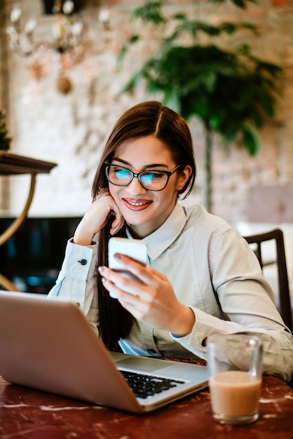 Smiling woman with eyeglasses using smartphone and laptop. Premium Photo