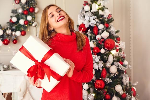 Donna sorridente con molti contenitori di regalo che posano vicino all'albero di natale decorato Foto Gratuite