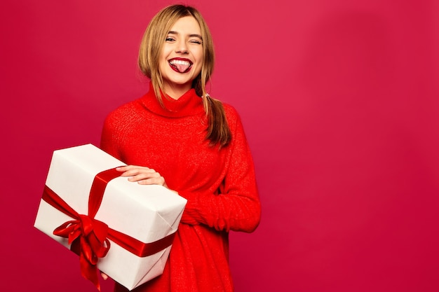 Smiling woman with many gift boxes posing on red wall Free Photo