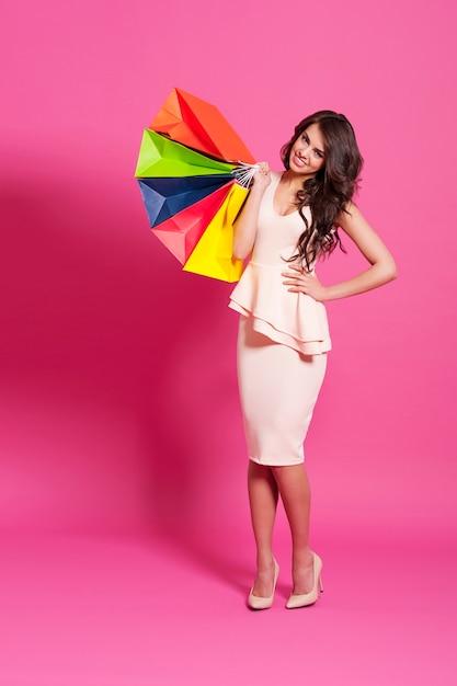 Улыбающаяся женщина с разноцветными сумками для покупок Бесплатные Фотографии