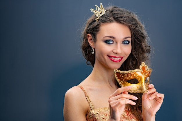 Smiling woman with a princess crown on her head and  holds a golden carnival mask in hands Premium Photo