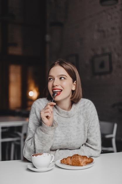 赤い口紅で笑顔の女性は小さじ1杯を舐めています。クロワッサンを楽しむカシミヤ衣装の女の子。 無料写真