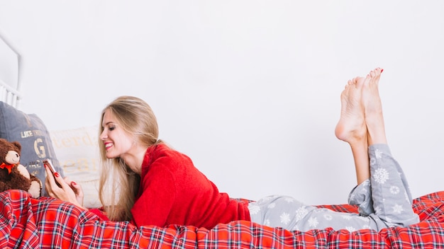 Smiling woman with smartphone lying on bed Free Photo