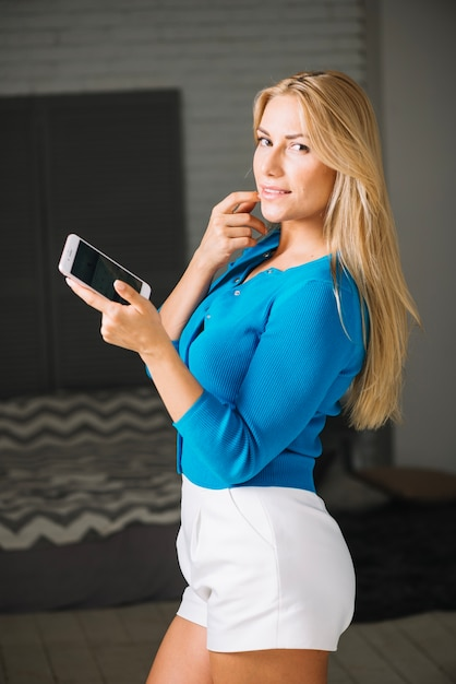 Smiling woman with smartphone Free Photo