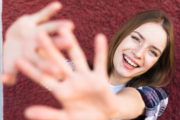 Smiling woman with stop gesture against red wall Free Photo