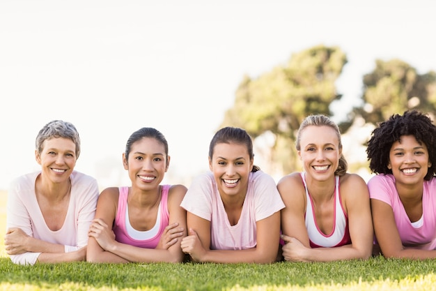 Smiling women lying in a row and wearing pink for breast cancer Premium Photo