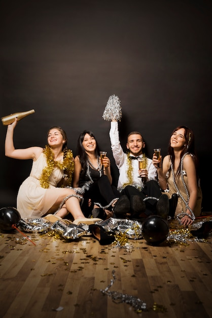 Smiling women and man in evening wear with glasses of drinks on floor Free Photo