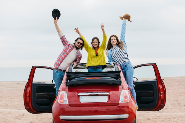 Smiling women near man with upped hands leaning out from car on shore Free Photo