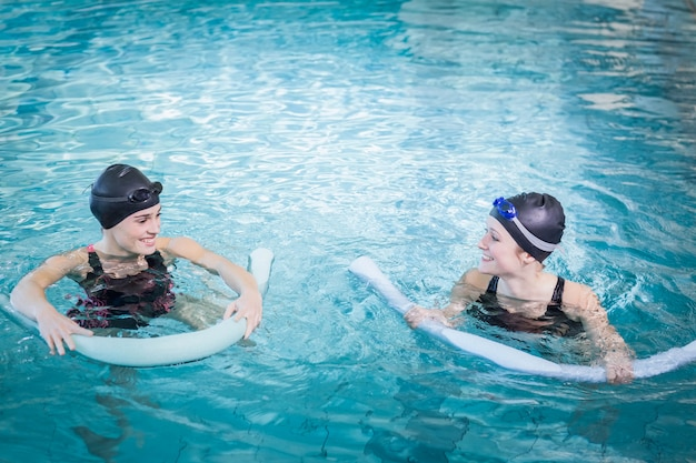 Smiling women in the pool with foam rollers at the leisure center Premium Photo