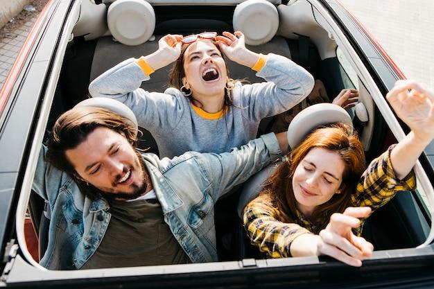 Smiling women and positive man having fun in car Free Photo