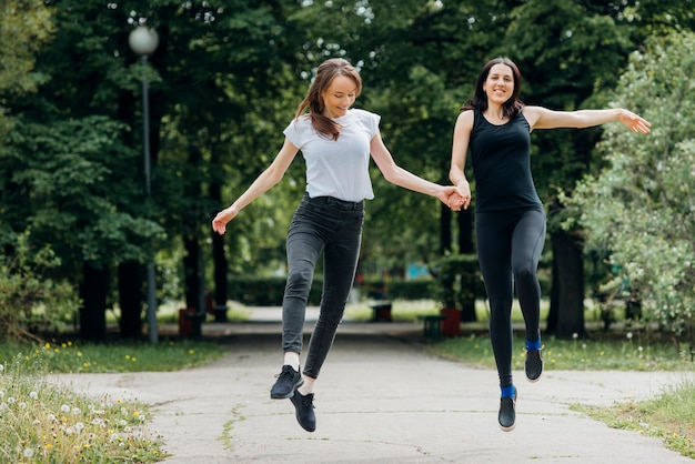Smiling women skipping and holding hands Free Photo