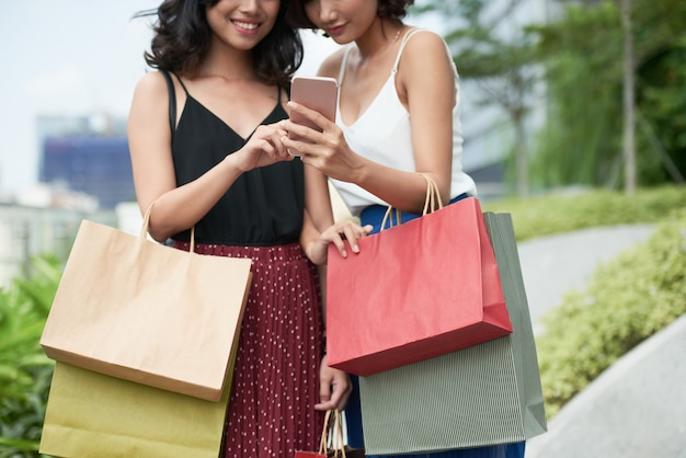 Smiling women with smartphone Free Photo