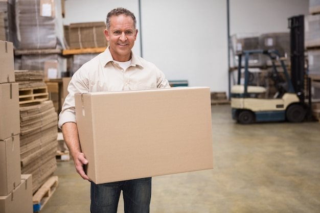 Smiling worker carrying a box Premium Photo